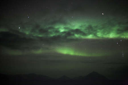 polar station: Northern lights behind clouds