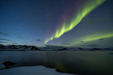 magnetosphere: The aurora borealis or the northern lights over the Arctic fjord