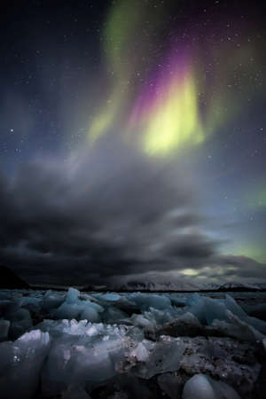 magnetosphere: The aurora borealis or the northern lights over the Arctic fjord - vertical landscape