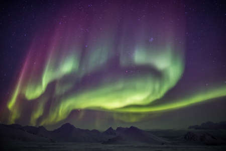 Natural phenomenon of Northern Lights (Aurora Borealis) related to the earths magnetic field, ionosphere and solar activity. Solar storm. Фото со стока