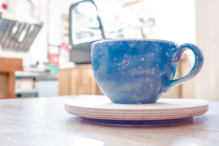 Blue Cup with tea or coffee on stand with blurred background