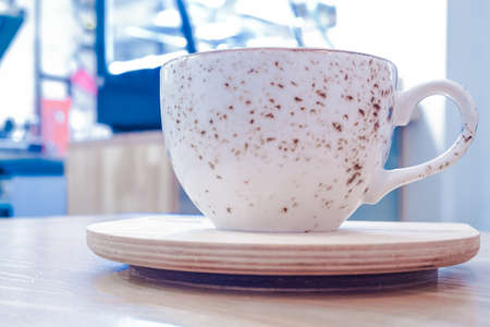 White Cup with tea or coffee on stand with blurred background