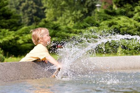 young boy playing in a public fountain photo