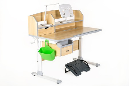 schooldesk: Wooden school table, green basket, desk lamp and support under legs on the white isolated background.