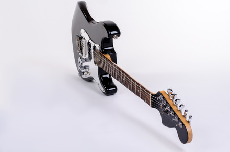 The classical form of black and white electric guitar is an edge with wooden maple neck, isolated on white background.