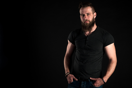 A charismatic and stylish man with a beard stands full-length on a black isolated background.