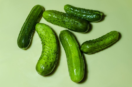 six green cucumbers on a light background Stock Photo