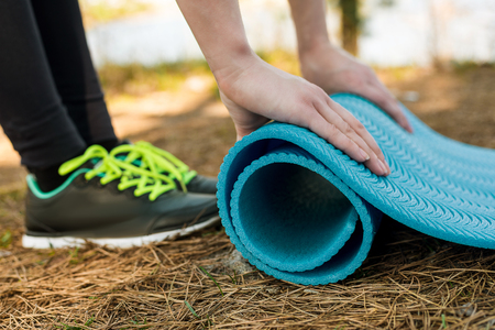 Girl in sports shoes spreads blue karemat, for yoga, warm-up or meditation