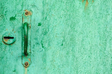 textured door handle on an old green door