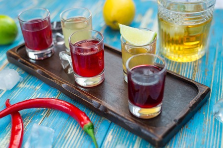 small glasses with colorful drinks on a wooden board Stock Photo