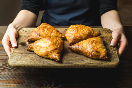 Uzbek national dish of samsa on a wooden board in the hands of a girl