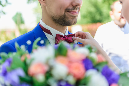 Groom in a blue suit with a red butterfly