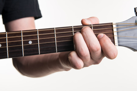 The guitarist's hand clamps the chord E on the guitar, on a white background
