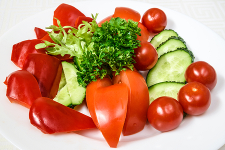 Tasty vegetable cut from tomatoes, cucumbers and peppers, with herbs