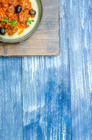 Frying pan with potatoes, minced meat, olives and herbs, on a wooden stand, stand on a blue denim background Banco de Imagens - 108866797