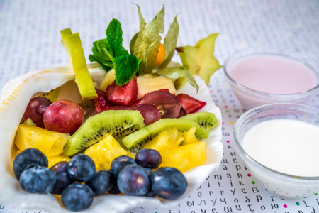 Kiwi, pineapple, strawberries and plums lie in a seashell with sauces Standard-Bild