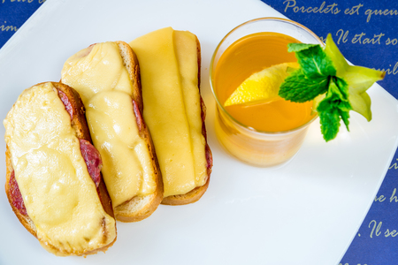 Bread with sausage and cheese and tea on a white plate