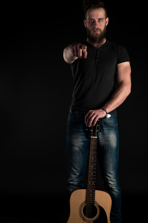 A charismatic and stylish man with a beard stands full-length with an acoustic guitar on a black isolated background.