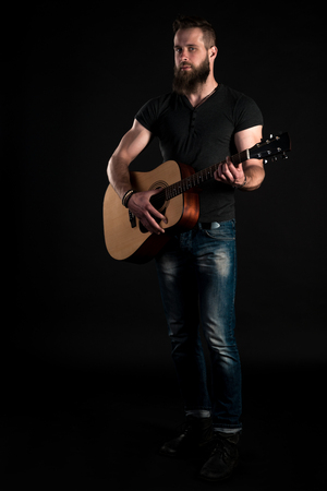 A charismatic and stylish man with a beard stands full-length and plays an acoustic guitar, on a black isolated background.