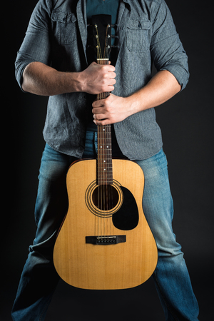 Men's hands hold an acoustic guitar