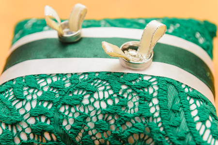 wedding rings lie on a green and white pillow