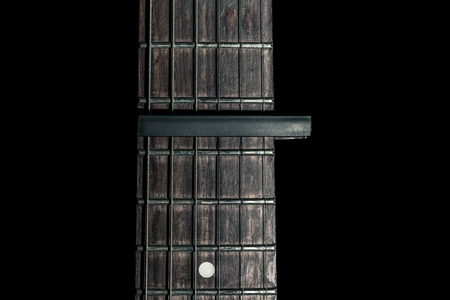 guitar part, neck with capo on a black background