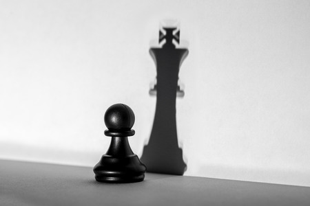 Chess pawn standing in a spotlight that make a shadow of king with darkness artistic conversion. Horizontal frame Фото со стока