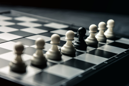 Chess board. Among the white pawns standing in a row is the black pawn of the enemy. Horizontal frame
