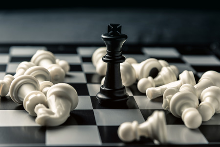Chess board. The black king among the defeated white chess of the opponent. Horizontal frame