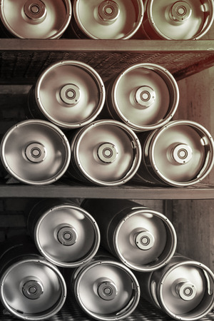 Metal beer kegs lie in a row on the shelf. Vertical frame