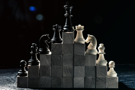Career ladder. chess from checkers to the king stand on wooden steps. Horizontal frame Standard-Bild - 116155518