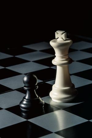 Chess board. White king threatens black opponent's pawn. Vertical frame Stok Fotoğraf - 116155477
