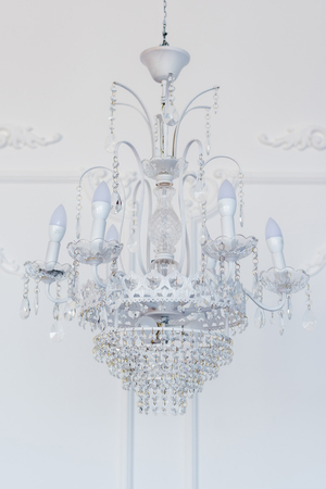 Large beautiful glass chandelier hanging on the ceiling. Vertical frame