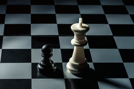 Chess board. White king threatens black opponents pawn. Horizontal frame