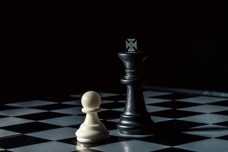 Chess board. Black king threatens white opponents pawn. Horizontal frame