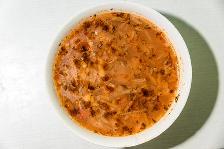 Ukrainian national dish, borsch in a white plate. Horizontal frame