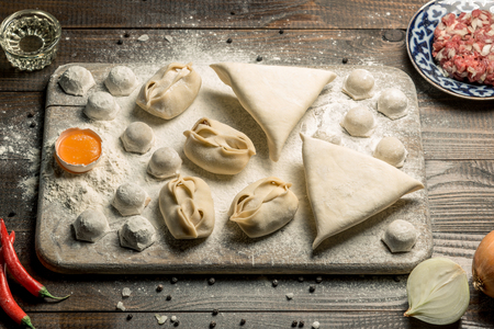 Traditional oriental, Uzbek cuisine, chuchvara, manti and samsa, a set of dishes made in one set. Horizontal frame Stock Photo