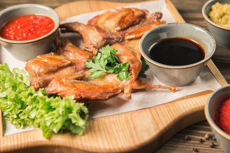 Roasted chicken on a plate with sauces and herbs. Horizontal frame 版權商用圖片