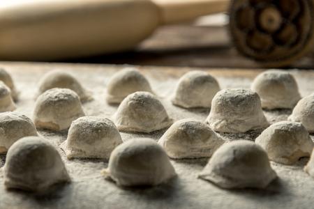 Uzbek national food Chuchvara, like dumplings, with a rolling pin, on a wooden board, in flour. Horizontal frame