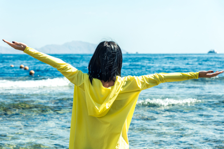 Travel and leisure, a girl with black hair in a yellow jacket stands against the blue sea with her arms spread to the sides. Horizontal frame
