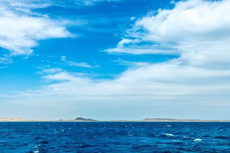 minimalistic seascape, blue sea and sky with white clouds on the whole frame. Horizontal frame