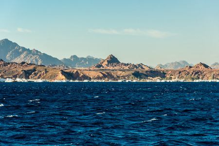 Seascape, view of the blue sea with high bald mountains in the background. Horizontal frame Stock Photo