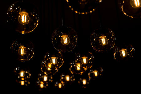 many burning incandescent bulbs hanging on the ceiling. Horizontal frame Stock Photo