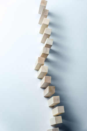 A long curved line of wooden cubes, as a symbol of a queue, competition for a position or team, on a uneven white background