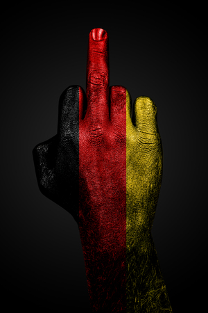 A hand with a painted flag of Germany shows the middle finger, a sign of aggression, against a dark background. Vertical frame Zdjęcie Seryjne
