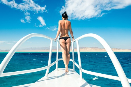 young girl standing on a white yacht in the blue sea. Horizontal frame