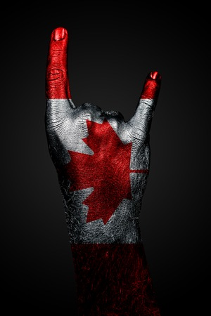 A hand with a drawn Canada flag shows a goat sign, a symbol of mainstream, metal and rock music, on a dark background. Vertical frame