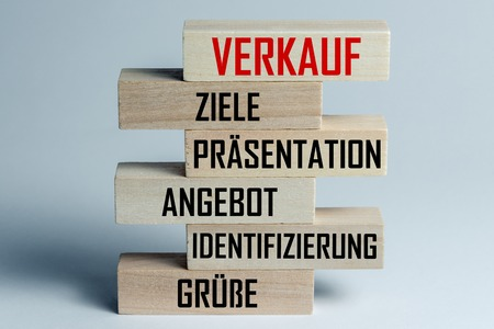 A list of wooden blocks lying on top of each other with a list of sales techniques in German, in the translation of the word: sale, objections, presentation, sentence, identification, greeting Stock Photo