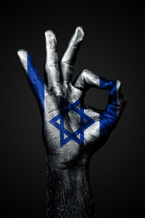A hand with the painted flag of Israel shows an OK sign on a dark background. Vertical frame
