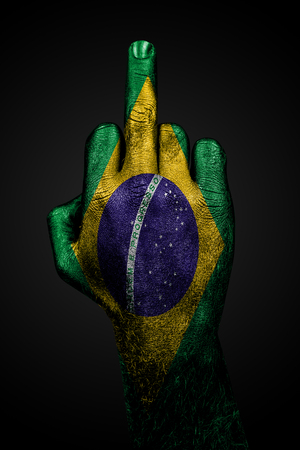 A hand with a painted flag of Brazil shows the middle finger, a sign of aggression, against a dark background. Vertical frame